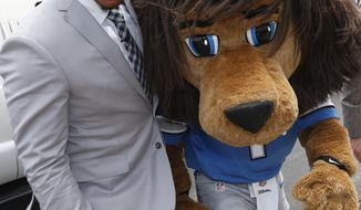 "Detroit Lions first round draft choice, 10th overall, North Carolina tight end Eric Ebron walks with team mascot ""Roary"" after arriving at the team's headquarters in Allen Park, Mich., Friday, May 9, 2014. (AP Photo/Paul Sancya)"