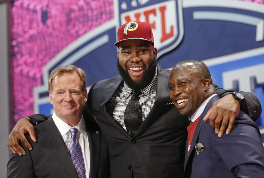 Virginia tackle Morgan Moses poses for photos with NFL commissioner Roger Goodell and former Washington Redskins' linebacker London Fletcher after being selected as the 66th pick during the third  round of the 2014 NFL Draft, Friday, May 9, 2014, in New York. (AP Photo/Jason DeCrow)
