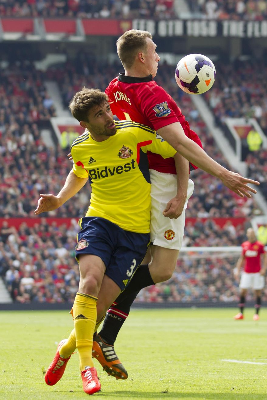 Manchester United's Phil Jones, right, fights for the ball against Sunderland's Fabio Borini, during their English Premier League soccer match at Old Trafford Stadium, Manchester, England, Saturday May 3, 2014. (AP Photo/Jon Super)