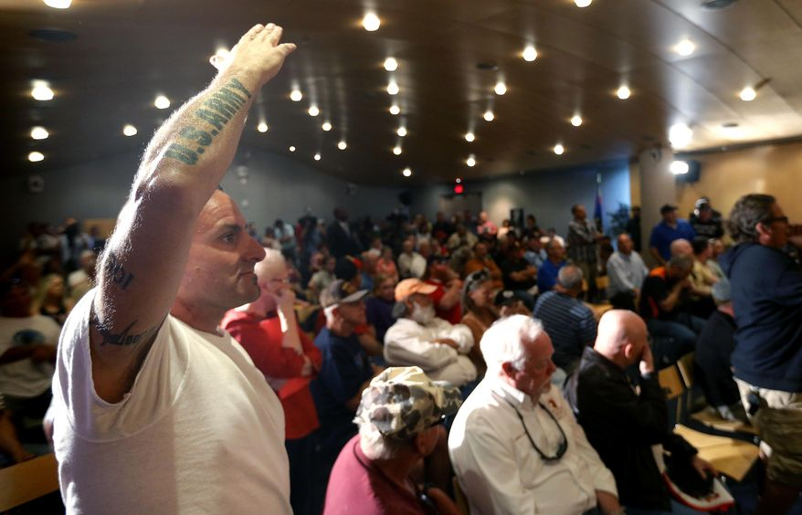 Veteran Mark Howey waits to ask a question as Sen. John McCain speaks during a forum with veterans on Friday, May 9, 2014, in Phoenix. McCain was discussing lapses in care at the Phoenix Veterans Affairs hospital that prompted a national review of operations around the country. (AP Photo/Matt York)
