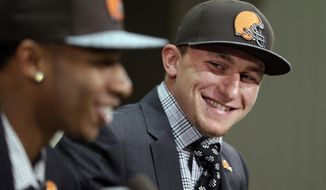 Cleveland Browns quarterback Johnny Manziel, right, from Texas A&M, watches cornerback Justin Gilbert during their introductory news conference at the NFL football team's facility in Berea, Ohio Friday, May 9, 2014. The Browns selected Gilbert with the eighth pick and Manziel with the 22nd pick in the first round of Thursday night's draft.  (AP Photo/Tony Dejak)
