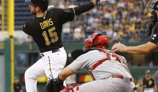 Pittsburgh Pirates' Ike Davis (15) watches the ball in front of St. Louis Cardinals catcher Yadier Molina after making a base hit, driving in two runs, in the first inning of a baseball game against the St. Louis Cardinals on Friday, May 9, 2014, in Pittsburgh. (AP Photo/Keith Srakocic)