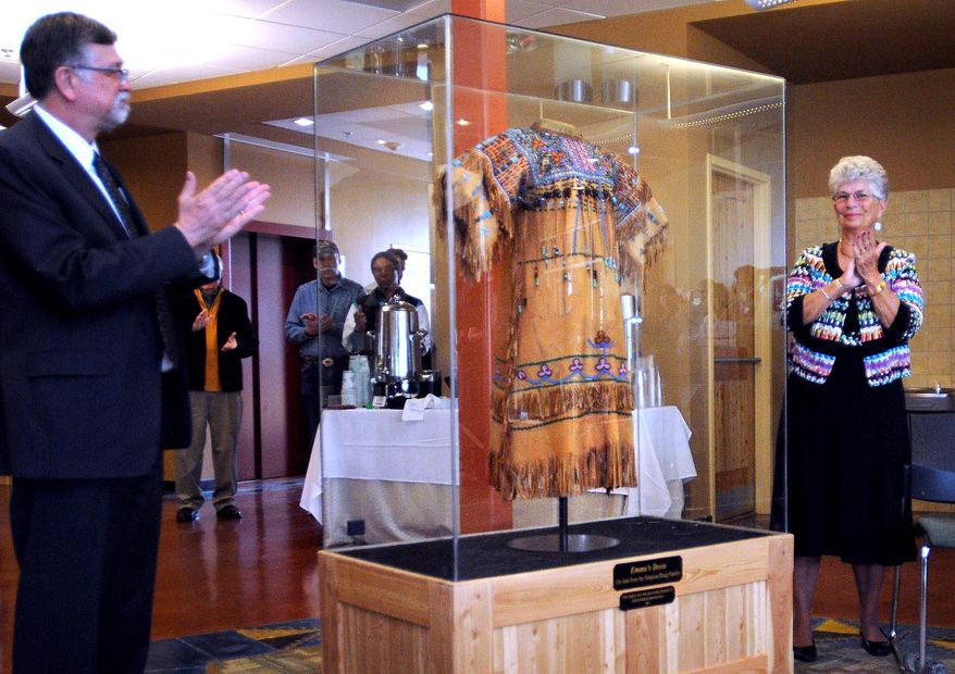 In this May 5, 2014 photo, Berverly Braig, right, claps after unveiling the dress made by her grandmother, Emma Sansaver, during a ceremony at the Payne Family Native American Center on the University of Montana campus in Missoula, Mont. Braig donated the dress to the university. (AP Photo/The Missoulian, Michael Gallacher)