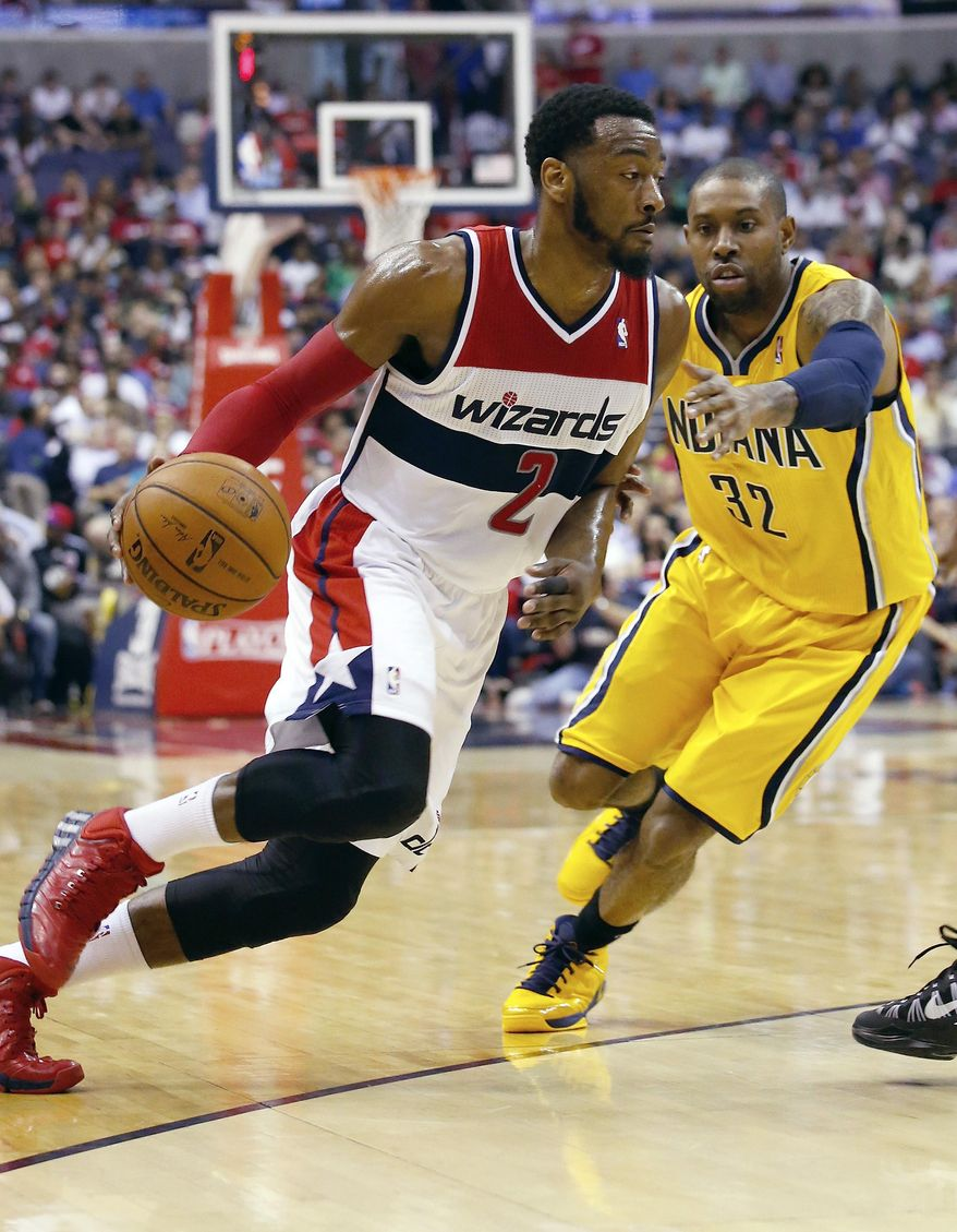 Washington Wizards guard John Wall (2) drives past Indiana Pacers guard C.J. Watson (32) during the first half of Game 3 of an Eastern Conference semifinal NBA basketball playoff game in Washington, Friday, May 9, 2014. (AP Photo/Alex Brandon)