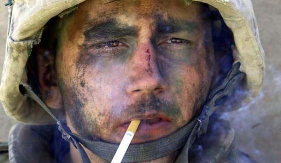 A member of Charlie Company of the U.S. Marines First Division, Eighth regiment, smokes a cigarette in Fallujah, Iraq, Tuesday, Nov. 9, 2004. U.S. forces punched into the center of the insurgent stronghold, overwhelming bands of guerrillas in the street with heavy barrages of fire and searching house to house in a powerful advance on the second day of a major offensive. (AP Photo/Los Angeles Times, Luis Sinco)