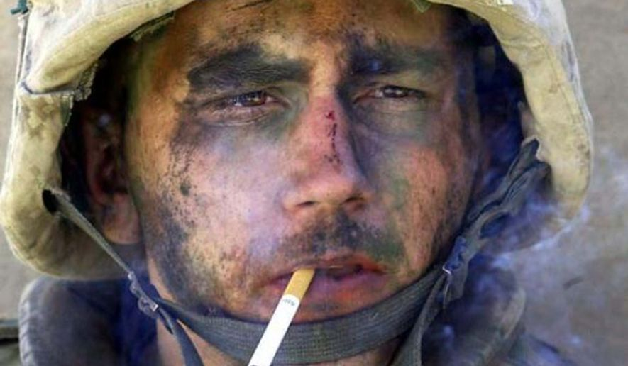 A member of Charlie Company of the U.S. Marines First Division, Eighth regiment, smokes a cigarette in Fallujah, Iraq, Tuesday, Nov. 9, 2004. U.S. forces punched into the center of the insurgent stronghold, overwhelming bands of guerrillas in the street with heavy barrages of fire and searching house to house in a powerful advance on the second day of a major offensive. (AP Photo/Los Angeles Times, Luis Sinco) ** FILE **