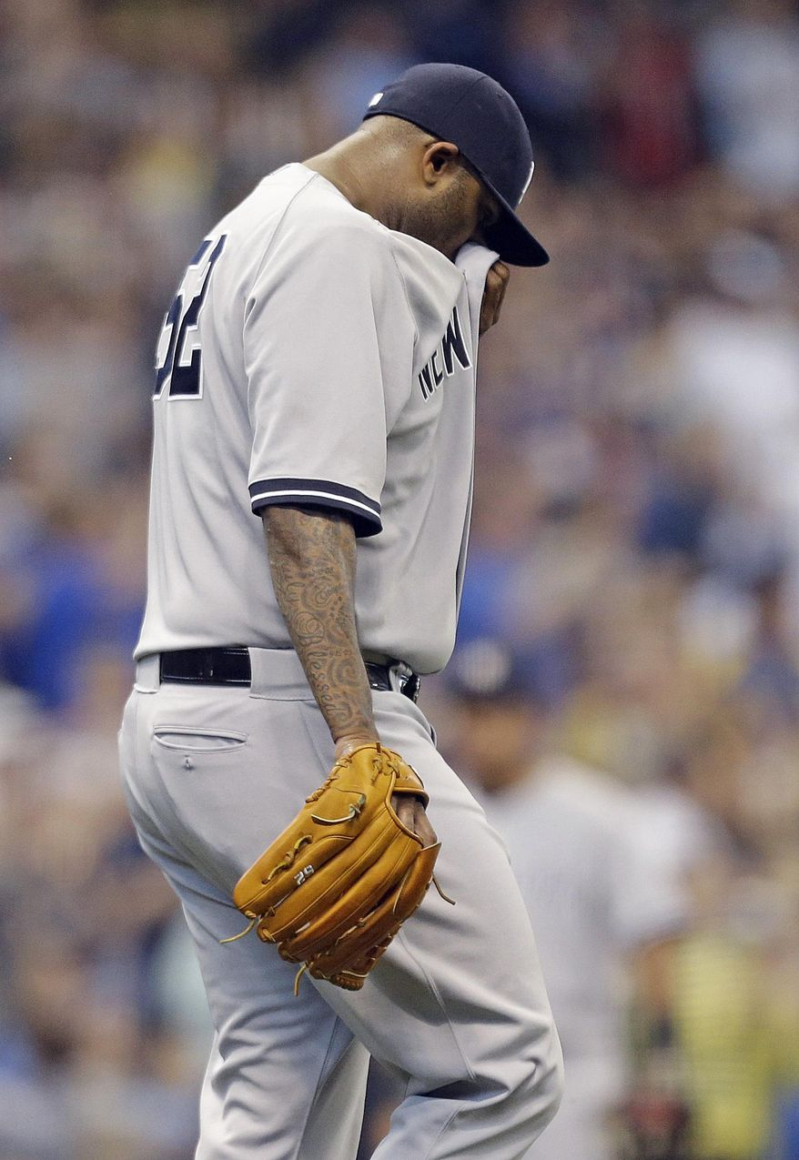 New York Yankees starting pitcher CC Sabathia wipes his face after giving up a home run to Milwaukee Brewers' Aramis Ramirez in the third inning of a baseball game Saturday, May 10, 2014, in Milwaukee. (AP Photo/Jeffrey Phelps)