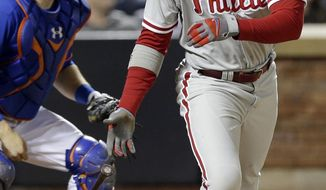 Philadelphia Phillies' Domonic Brown follows through on an RBI single during the third inning of a baseball game against the New York Mets, Friday, May 9, 2014, in New York. (AP Photo/Frank Franklin II)