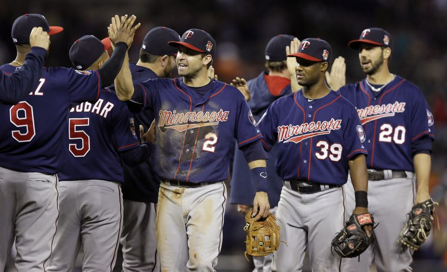 Minnesota Twins second baseman Brian Dozier (2), shortstop Danny Santana (39) and right fielder Chris Colabello (20) celebrate their 2-1 win over the Detroit Tigers with teammates after a baseball game in Detroit, Friday, May 9, 2014. (AP Photo/Carlos Osorio)