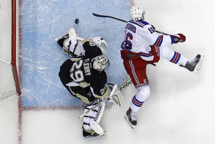 New York Rangers' Derick Brassard (16) backhands a shot past Pittsburgh Penguins goalie Marc-Andre Fleury (29) in the first period of Game 5 of a second-round NHL playoff hockey series in Pittsburgh, Friday, May 9, 2014. The Rangers won 5-1. (AP Photo/Gene J. Puskar)