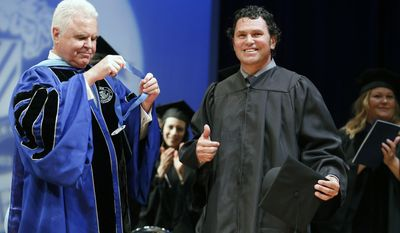Boston Marathon bombing specttor Carlos Arredondo reacts after receiving an honorary degree from the  president of Fisher College Dr. Thomas McGovern, left, during commencement ceremonies in Boston, Saturday, May 10, 2014. Arredondo and bombing survivor Jeff Bauman, who'se life Arredondo saved the day of the bombing, each gave graduation speeches and were awarded honorary degrees.   (AP Photo/Michael Dwyer)