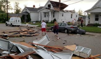 People walk through debris after a storm in Evansville, Ind., Friday, May 9, 2014. (AP Photo/The Evansville Courier & Press, Kevin Swank)
