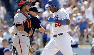 Los Angeles Dodgers' Yasiel Puig (66) scores with San Francisco Giants catcher Hector Sanchez, left, and home plate umpire Mark Carlson, center, looking on after a single hit by Dodgers' Matt Kemp in the sixth inning of a baseball game on Saturday, May 10, 2014, in Los Angeles. (AP Photo/Alex Gallardo)