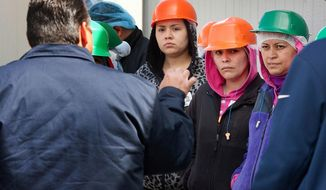 Hector Calderon, foreground, a manager for the Crunch Pak sliced apple company, speaks to workers demonstrating outside the production warehouse in Cashmere, Wash., on Friday, May 9, 2014. They walked away from work in a protest because a number of them may be taken off the job due to an U.S. Immigration and Customs Enforcement audit in August 2013. (AP Photo/The Wenatchee World, Don Seabrook)