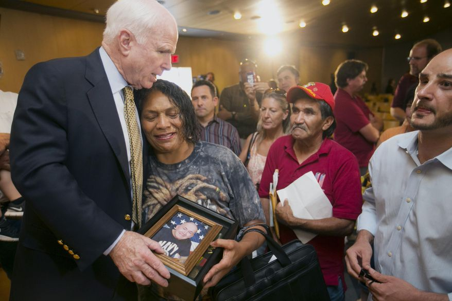 Sen. John McCain, left, R-Ariz., hugs Sherri Jordan as she holds photograph of her husband, Manuel Acosta, during a forum with veterans on Friday, May 9, 2014, in Phoenix. Jordan said Acosta is a cancer patient that has not received adequate care from Phoenix VA Health Care System. McCain was at the forum discussing lapses in care at the Phoenix Veterans Affairs hospital that prompted a national review of operations around the country. (AP Photo/The Arizona Republic, David Wallace)  MARICOPA COUNTY OUT; MAGS OUT; NO SALES