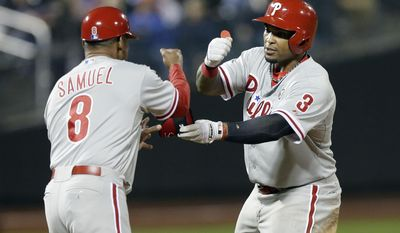 Philadelphia Phillies' Marlon Byrd (3) hands his elbow guard to first base coach Juan Samuel (8) after driving in a run during the eleventh inning of a baseball game against the New York Mets, Friday, May 9, 2014, in New York. (AP Photo/Frank Franklin II)