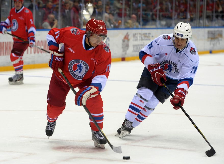 Russian President Vladimir Putin, left, controls the puck during an ice hockey match between Russian amateur players and ice hockey stars at a festival of Russia's amateur hockey organized by the Night Hockey League in the Bolshoy arena in the  Olympic Park in the Black Sea resort of Sochi, Russia, Saturday May 10, 2014. (AP Photo/RIA-Novosti, Alexei Druzhinin, Presidential Press Service)
