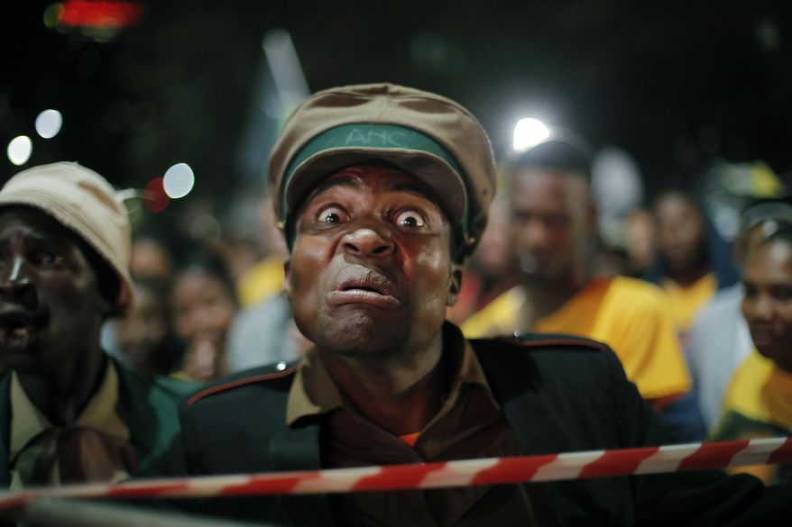 An ANC supporter waits for the ruling party president Jacob Zuma to arrive at a victory party downtown Johannesburg, South Africa,   following the announcement of the results for the 2014 national election result Saturday May 10, 2014. South Africa's election commission completed a vote count that confirms the ruling African National Congress as the winner but also shows the strengthening of prominent opposition groups.  (AP Photo/Jerome Delay)