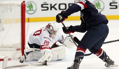 Switzerland goaltender Reto Berra makes a save in front of USA forward Tim Stapleton during the Group B preliminary round match between Switzerland and USA at the Ice Hockey World Championship in Minsk, Belarus, Saturday, May 10, 2014. (AP Photo/Darko Bandic)
