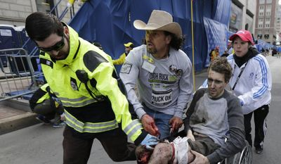 FILE - In this April 15, 2013 file photo, an emergency responder and volunteers, including Carlos Arredondo, center, in the cowboy hat, push Jeff Bauman in a wheel chair after he was injured in an explosion near the finish line of the Boston Marathon, in Boston. On Saturday, May 10, 2014, Arredondo and Bauman both received honorary degrees and gave graduation speeches during commencement ceremonies for Fisher College in Boston.  (AP Photo/Charles Krupa, File)