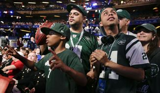 New York Jets fans listen for the Jets' fourth-round selection at the 2014 NFL Draft, Saturday, May 10, 2014, in New York. The Jets picked Oklahoma wide receiver Jalen Saunders. (AP Photo/Julie Jacobson)