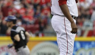 Cincinnati Reds starting pitcher Alfredo Simon, right, stands on the mound after giving up a home run to Colorado Rockies' Corey Dickerson (6) in the first inning of a baseball game on Saturday, May 10, 2014, in Cincinnati. (AP Photo/Al Behrman)