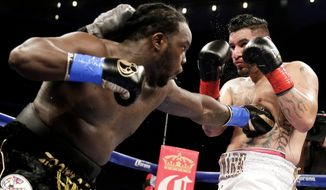 Bermane Stiverne, left, hits Chris Arreola during their rematch for the WBC heavyweight boxing title in Los Angeles, Saturday, May 10, 2014. Stiverne won the title. (AP Photo/Chris Carlson)