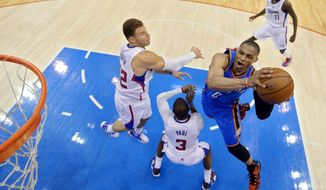 Oklahoma City Thunder guard Russell Westbrook, right, shoots as Los Angeles Clippers forward Blake Griffin, left, and guard Chris Paul (3) defend and guard Jamal Crawford looks on in the second half of Game 3 of the Western Conference semifinal NBA basketball playoff series, Friday, May 9, 2014, in Los Angeles. The Thunder won 118-112. (AP Photo/Mark J. Terrill)