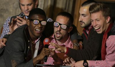 Bayern's David Alaba of Austria, from left, Franck Ribery of France, Diego Contento and Mitchell Weiser celebrate on the town hall balcony after winning the German Soccer Championship after the season's last home game between FC Bayern Munich and VfB Stuttgart, in Munich, southern Germany, Saturday, May 10, 2014. (AP Photo/Matthias Schrader)