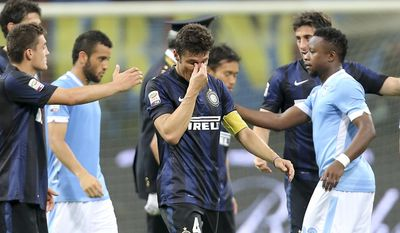 Inter Milan's Javier Zanetti,of Argentina, center, wipes his eyes at the end of the Serie A soccer match between Inter Milan and Lazio at the San Siro stadium in Milan, Italy, Saturday, May 10, 2014. Zanetti will retire after 19 seasons at Inter, and the stadium was sold out as fans packed in to bid farewell to their 40-year-old captain. (AP Photo/Antonio Calanni)