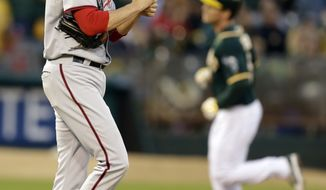 Washington Nationals' Doug Fister, left, walks back to the mound after giving up a home run to Oakland Athletics' John Jaso, right, in the third inning of a baseball game on Friday, May 9, 2014, in Oakland, Calif. (AP Photo/Ben Margot)