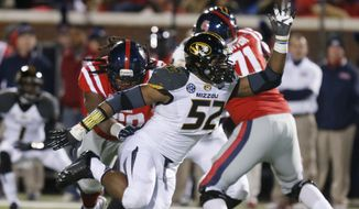 FILE - In this Nov. 23, 2013, file photo, Missouri defensive lineman Michael Sam (52) pushes past a block by Mississippi offensive linesman Pierce Burton (71) during the second half of an NCAA college football game in Oxford, Miss. The NFL draft will conclude with Rounds 4 through 7 on Saturday, and when and if Sam is selected is sure to be the most significant development. The Southeastern Conference defensive player of the year last season for Missouri came out as gay in media interviews this year.    (AP Photo/Rogelio V. Solis, File)