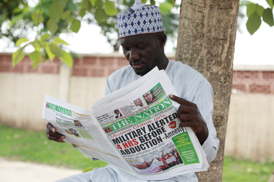 Shehu Haruna reads a local newspaper with headlines declaring that the military were alerted before the abduction of secondary school girls in Chibok, on a street in Abuja, Nigeria, Saturday, May 10, 2014. (AP Photo/Sunday Alamba)