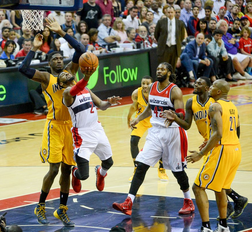 Indiana Pacers center Roy Hibbert (55) fouls Washington Wizards guard John Wall (2) as he drives for a shot in the third quarter as the Washington Wizards lose to the Indiana Pacers 85-63 in game 3 during the second round of the Eastern Conference Semifinal NBA basketball playoffs at the Verizon Center, Washington, D.C., Friday, May 9, 2014. (Andrew Harnik/The Washington Times)