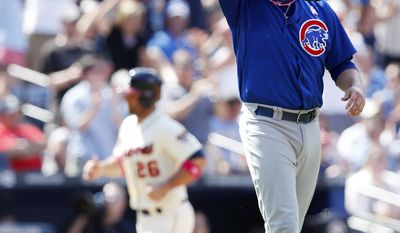 Chicago Cubs relief pitcher James Russell, right,wipes his face as Atlanta Braves' Dan Uggla (26) rounds third base to score on a Jason Heyward home run in the seventh inning of a baseball game on Sunday, May 11, 2014, in Atlanta. (AP Photo/John Bazemore)