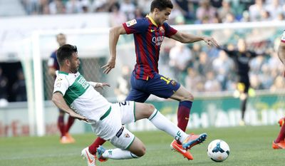 Barcelona's Marc Bartra duels for the ball with Elche's Domingo Cisma Gonzalez during a Spanish La Liga soccer match at the Martinez Valero stadium in Elche, Spain, on Sunday, May 11, 2014. (AP Photo/Alberto Saiz)