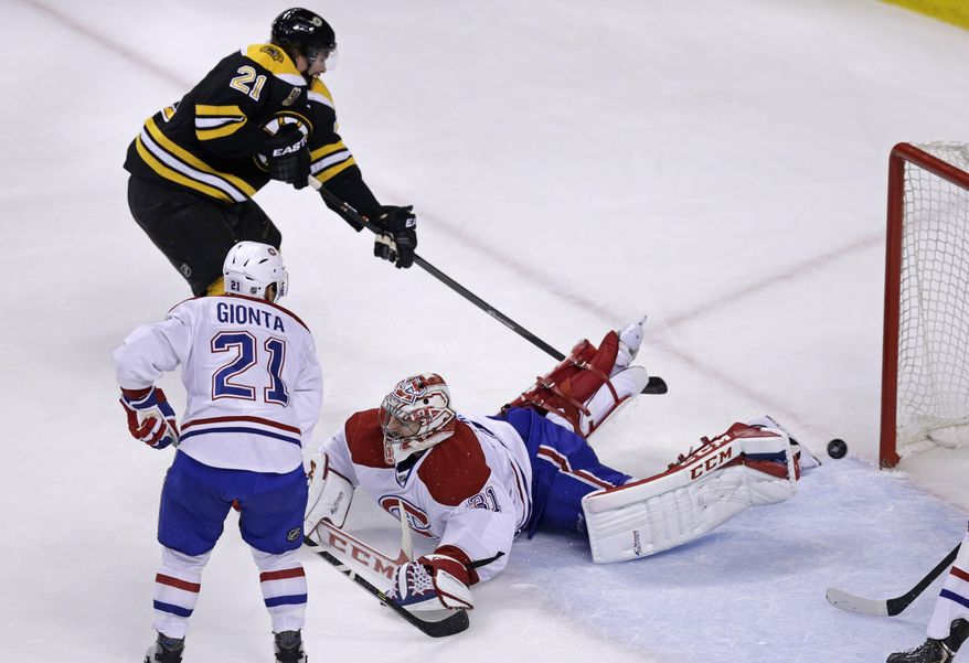 Boston Bruins left wing Loui Eriksson, top, beats Montreal Canadiens goalie Carey Price (31) as he scores during the third period of Game 5 in the second-round of the Stanley Cup hockey playoff series in Boston, Saturday, May 10, 2014. (AP Photo/Charles Krupa)