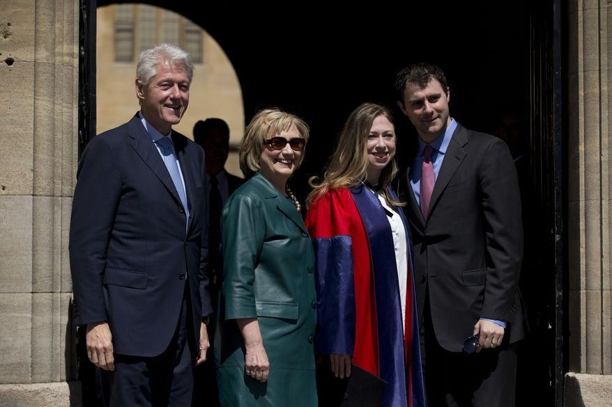 Former U.S. Secretary of State Hillary Rodham Clinton, second left, before taking her sunglasses off poses for a group photograph with her husband former U.S. President Bill Clinton, left, their daughter Chelsea, third left, and her husband Marc Mezvinsky, after they all attended Chelsea's Oxford University graduation ceremony at the Sheldonian Theatre in Oxford, England, Saturday, May 10, 2014.  Chelsea Clinton received her doctorate degree in international relations on Saturday from the prestigious British university. Her father was a Rhodes scholar at Oxford from 1968 to 1970.  The graduation ceremony comes as her mother is considering a potential 2016 presidential campaign.  (AP Photo/Matt Dunham)