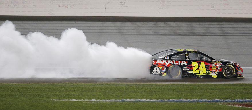 NASCAR driver Jeff Gordon (24) celebrates after winning the Sprint Cup Series auto race at Kansas Speedway in Kansas City, Kan., Saturday, May 10, 2014. (AP Photo/Orlin Wagner)
