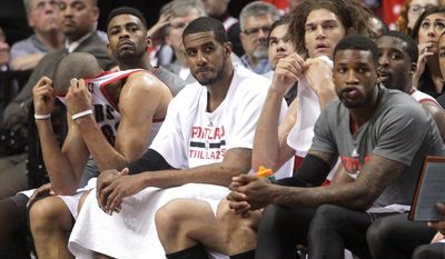 From left, Portland Trail Blazers' Nicolas Batum, Dorell Wright, LaMarcus Aldridge, Robin Lopez, Thomas Robinson and Wesley Matthews watch from the bench in the final minute of their Game 3 of a Western Conference semifinal NBA basketball playoff series against the San Antonio Spurs, Saturday, May 10, 2014, in Portland, Ore. The Spurs won 118-103. (AP Photo/Rick Bowmer)