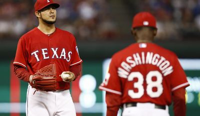 Texas Rangers manager Ron Washington (38) heads to the mound to relieve pitcher Martin Perez (33) during the fourth inning of a baseball game against the Boston Red Sox, Saturday, May 10, 2014, in Arlington, Texas. (AP Photo/Jim Cowsert)