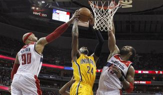 Washington Wizards forward Drew Gooden (90) and Washington Wizards forward Nene from Brazil (42) block Indiana Pacers forward Paul George's (24) shot at the basket during the first half of Game 4 of an Eastern Conference semifinal NBA basketball playoff game in Washington, Sunday, May 11, 2014. (AP Photo/Alex Brandon)