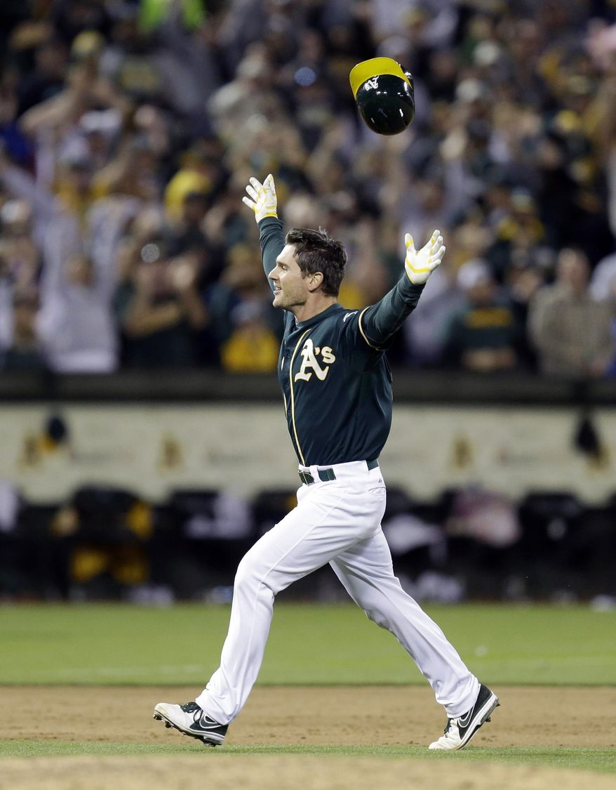 Oakland Athletics' John Jaso celebrates after making the game-winning hit against the Washington Nationals in the 10th inning of a baseball game Saturday, May 10, 2014, in Oakland, Calif. (AP Photo/Ben Margot)