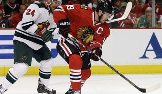 Chicago Blackhawks' Jonathan Toews (19), right, controls the puck against Minnesota Wild's Matt Cooke (24) during the first period  in Game 5 of an NHL hockey second-round playoff series in Chicago,Sunday, May 11, 2014. (AP Photo/Nam Y. Huh)