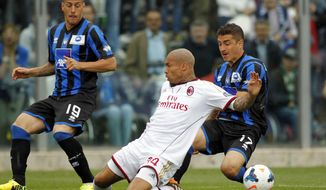 AC Milan's Nigel De Jong, center, of the Netherlands, fights for the ball with Atalanta's Carlos Carmona, right, of Chile, as Atalanta's German Denis, left, of Argentina, during a Serie A soccer match in Bergamo, Italy, Sunday, May 11, 2014. (AP Photo/Felice Calabro')
