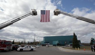 "The American Flag hangs from two fire department ladder trucks during the memorial service for Alaska State Trooper Sgt. Patrick ""Scott"" Johnson and Trooper Gabriel ""Gabe"" Rich at the Carlson Center, Saturday, May 10, 2014m in Fairbanks, Alaska. The tow were killed in the line of duty in the village of Tanana earlier this month. (AP Photo/The Fairbanks Daily News-Miner, Eric Engman)"