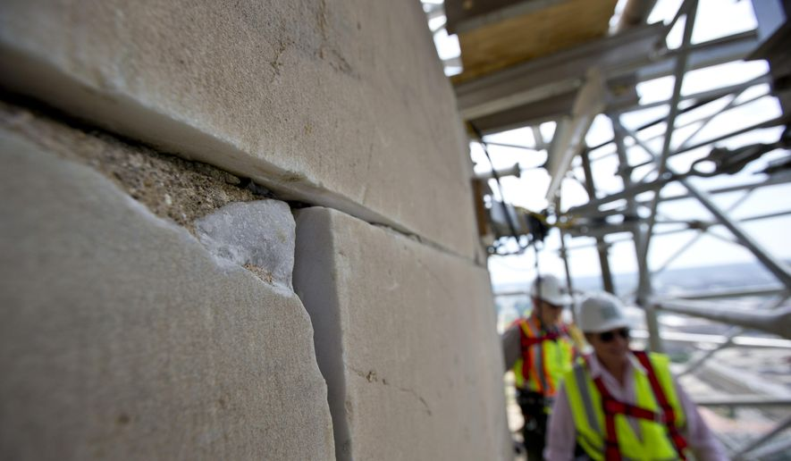 This June 2, 2013, file photo shows a damaged stone on the Washington Monument at the 491-foot level of the scaffolding surrounding the monument, in Washington. The monument, which sustained damage from an earthquake in August 2011, reopened to the public on Monday, May 12, 2014. (AP Photo/Alex Brandon, File)