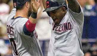 Cleveland Indians' Yan Gomes, left, and Nyjer Morgan, right, celebrate after scoring on Michael Bourn's two-run double during the second inning of a baseball game against the Tampa Bay Rays, Sunday, May 11, 2014, in St. Petersburg, Fla. (AP Photo/Steve Nesius)