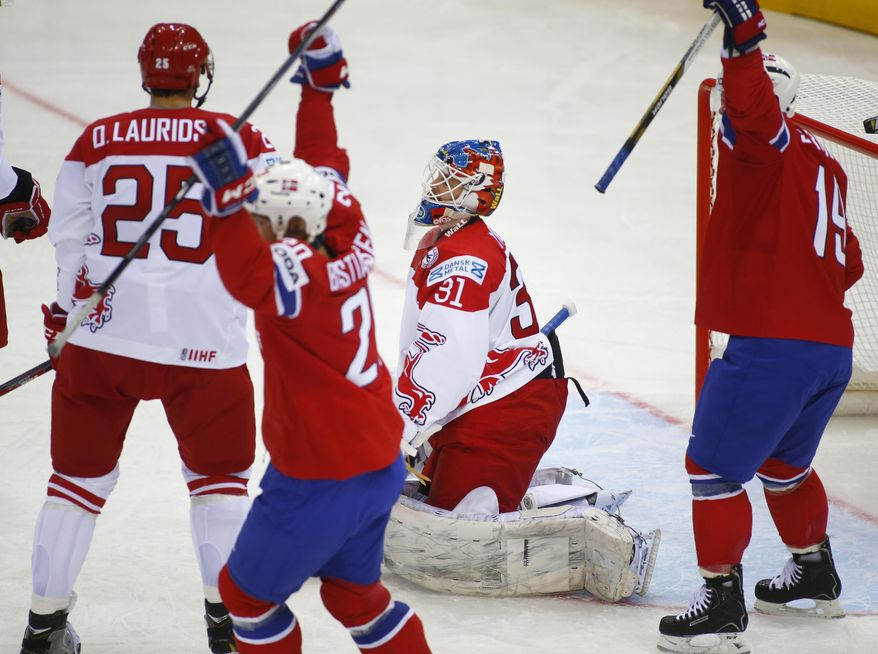 Denmark's goalie Simon Nielsen, center, reacts after Norway's Jonas Holos scored during the Group A preliminary round match at the Ice Hockey World Championship in Minsk, Belarus, Sunday, May 11, 2014. (AP Photo/Sergei Grits)