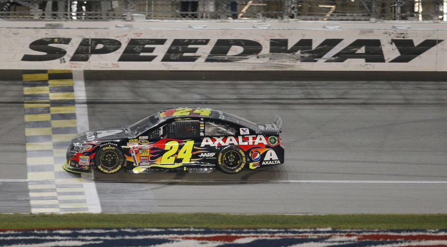 NASCAR driver Jeff Gordon (24) crosses the finish line to win the Sprint Cup Series auto race at Kansas Speedway in Kansas City, Kan., Saturday, May 10, 2014. (AP Photo/Orlin Wagner)